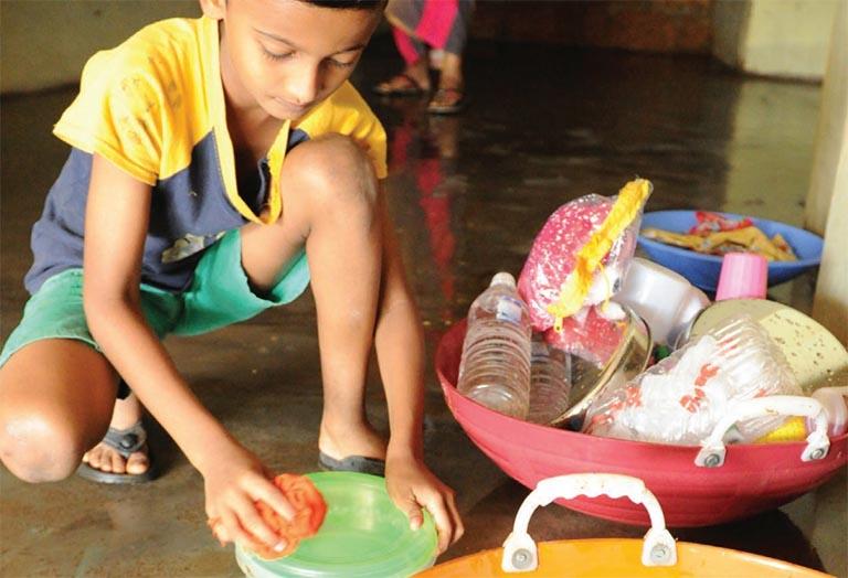 കാവുമ്പായി അലക്സ് നഗറിൽ വെള്ളം ഇറങ്ങിയപ്പോൾ സ്കൂളിലേക്കു ചോറുകൊണ്ടുപോകുന്ന പാത്രം  വൃത്തിയാക്കുന്ന കുട്ടി          ഫോട്ടോ/ജഗത്ലാൽ